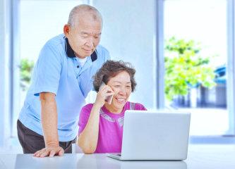 happy elderly couple using a laptop