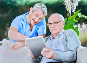 male caregiver assist the senior man using a tablet