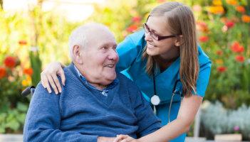 caregiver and senior man holding hands